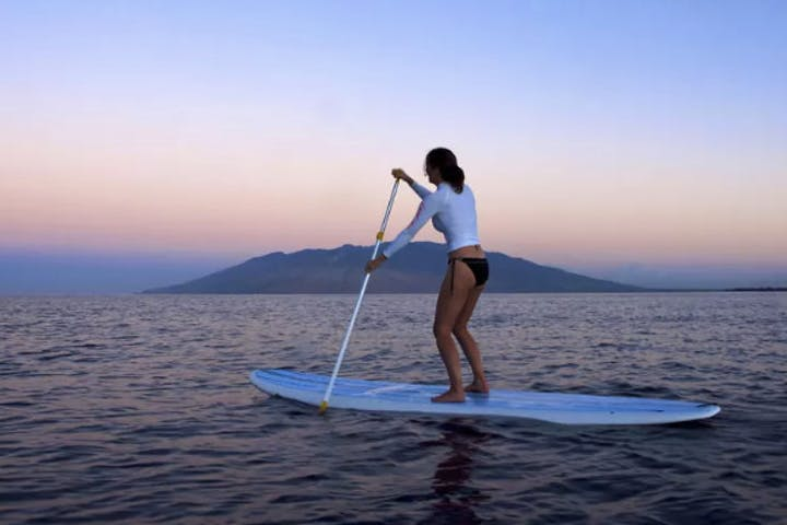 Woman on paddleboard at dusk