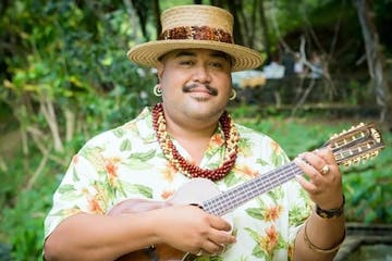 Polynesian man playing a ukulele