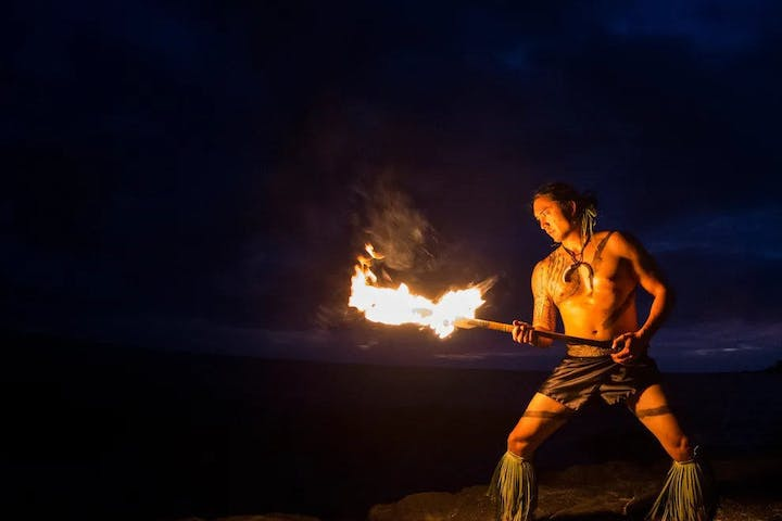 Polynesian man with a fire knife in the dark