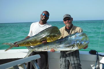 two men holding fish in punta cana