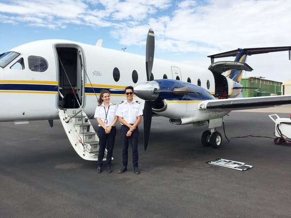Two pilots standing behind the plane
