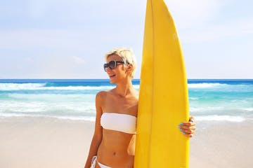 woman on beach with yellow surfboard