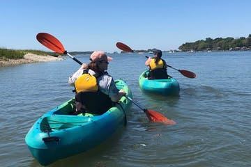 two kayakers exploring the coastal area