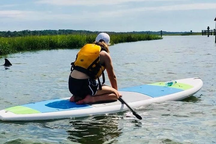 woman sitting on a paddle board in the river