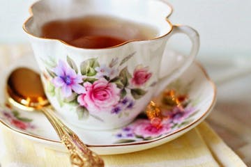A cup of tea served in an ornate china tea cup.