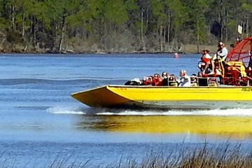 humans on a yellow airboat