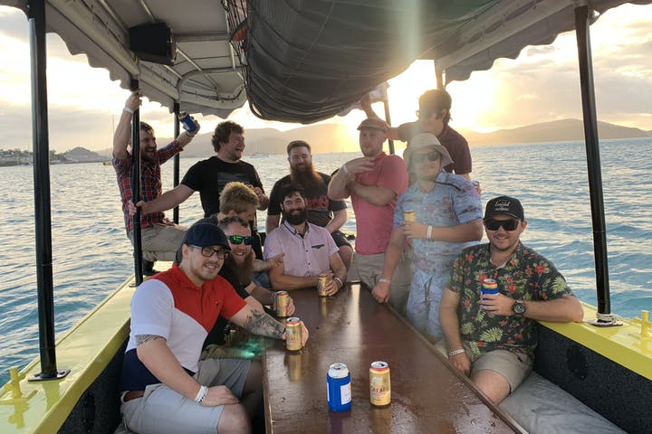 group posing on boat during sunset