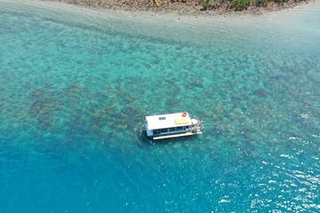 a blue and white boat sitting next to a body of water