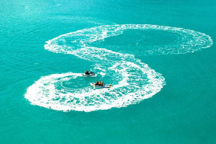Jet Boat and Banana boat combo, a drone photo of a banana boat ride in Airlie Beach, The Whitsundays.