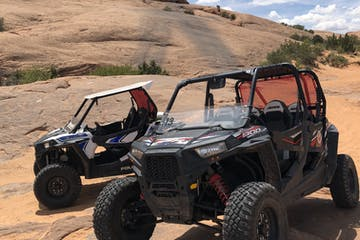 two rzrs parked on rocky cliff