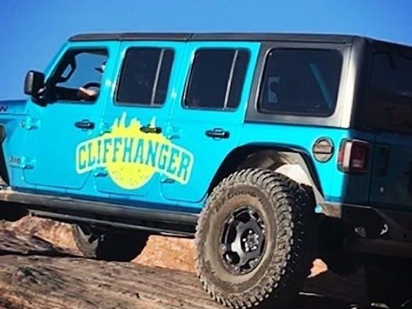a blue truck driving down a dirt road