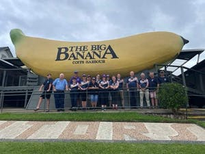 a group of people standing around a plane with Big Banana in the background