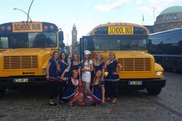a group of people standing in front of a school bus