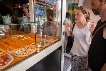Eine Frau und ein Mann vor einem Pizza-Laden