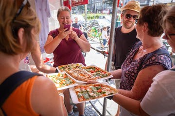 Ein paar Frauen die Pizza-Stücke in ihren Händen halten