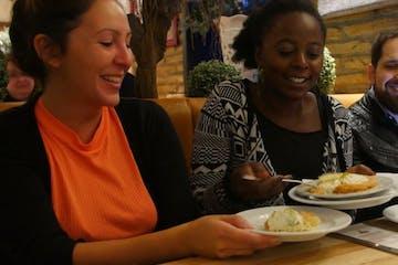 Drei Leute mit Essen und Tellern an einem Tisch