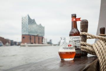 Eine Flasche und ein Glas mit dem Störtebeker Bierlogo