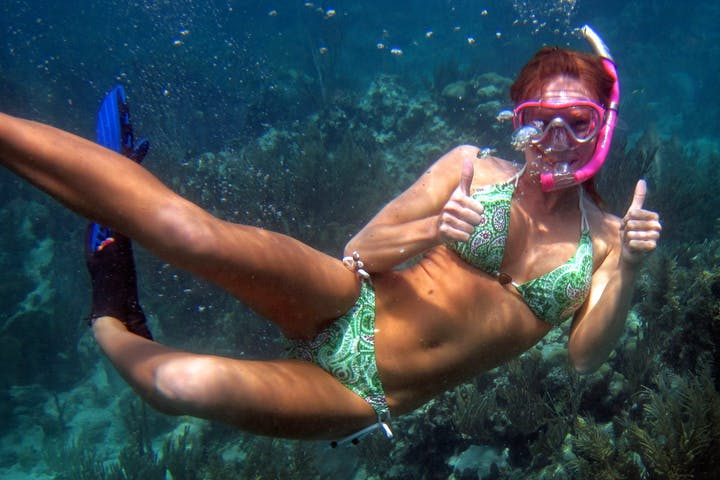 girl underwater giving thumbs up to camera