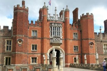 a large brick building with Hampton Court Palace in the background