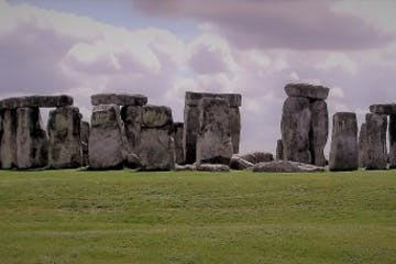 a large stone building with a grassy field with Stonehenge in the background