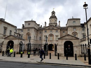 a group of people walking in front of Horse Guards