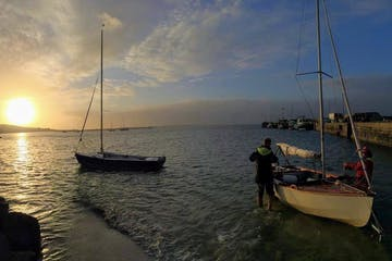 two boats in the water during sunset