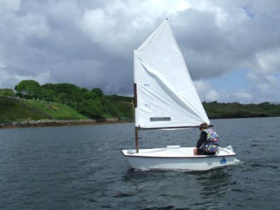 little boy sailing with a white boat in Ireland