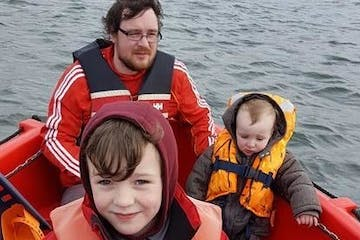dad with two sons on boat