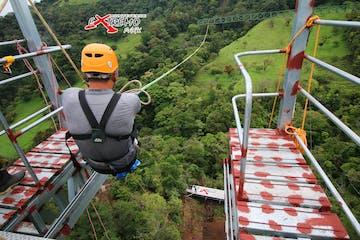a man jumping off the Monteverde Extremo Mega Swing Platform