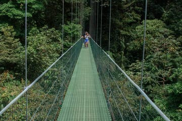 Two tourists walking on a Hanging Bridge in Monteverde Costa Rica