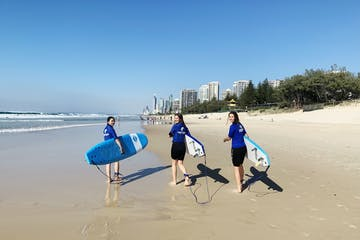 3 girls walking while holding their surfboards