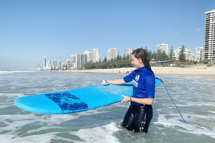 Girl holding her surfboard on the beach