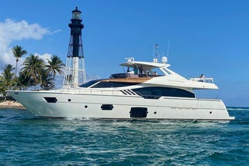 Yacht rental in Fort Lauderdale cruising past a lighthouse.