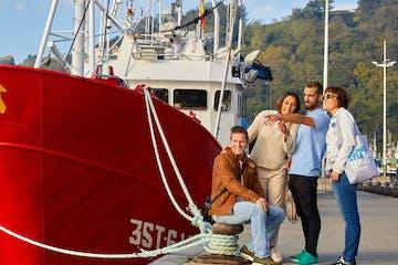 grupo de gente al lado de un barco rojo