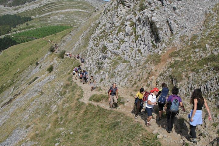 grupo caminando por un camino de una montaña vasca