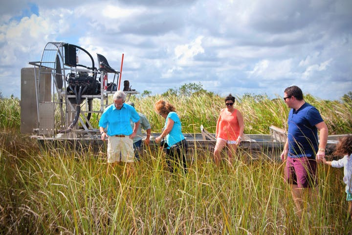 tour group next to airboat in swamp