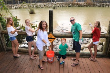 family smiling in front of alligator exhibit