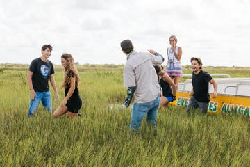 a group of people standing in the everglades