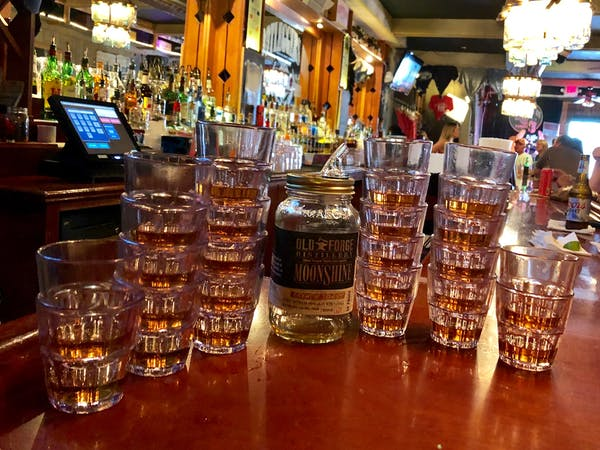 Beer and shot glasses stacked on a bar top after Nashville bachelorette party, food tour, and pub crawl near me