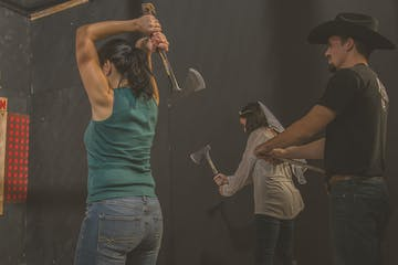 Man grading women throwing axes