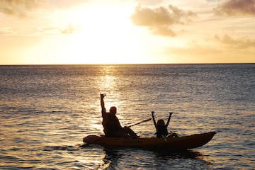 Two kayakers posing on the ocean during a sunset in Hawaii
