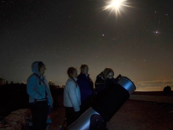 A group of people looking up at the sky.