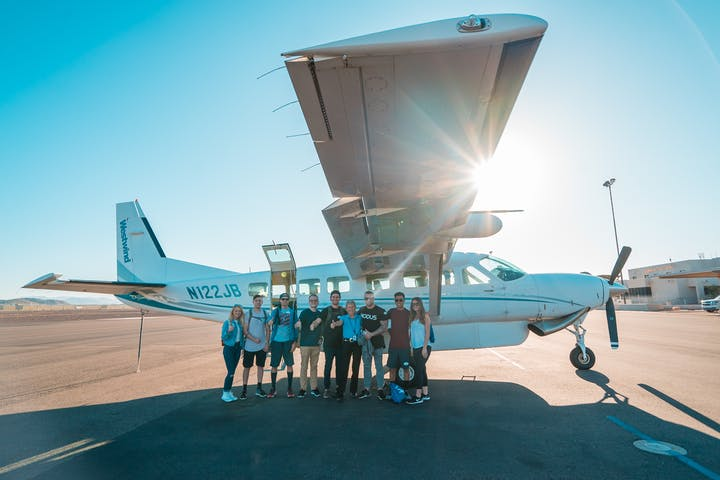 group of people standing in front of tour plane
