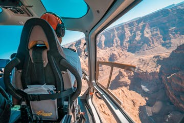 Man sitting in cockpit of helicopter while flying over the Grand Canyon