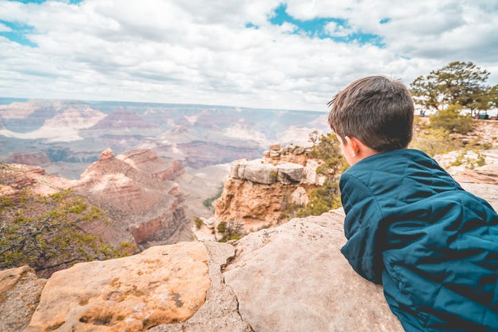 little boy laying on ledge of lookout of the Grand Canyon