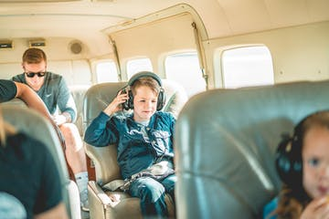 Little boy putting on headphones inside plane