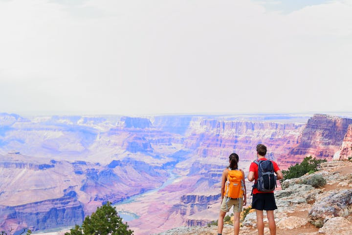 two hikers standing on canyon ledge looking out at scenery