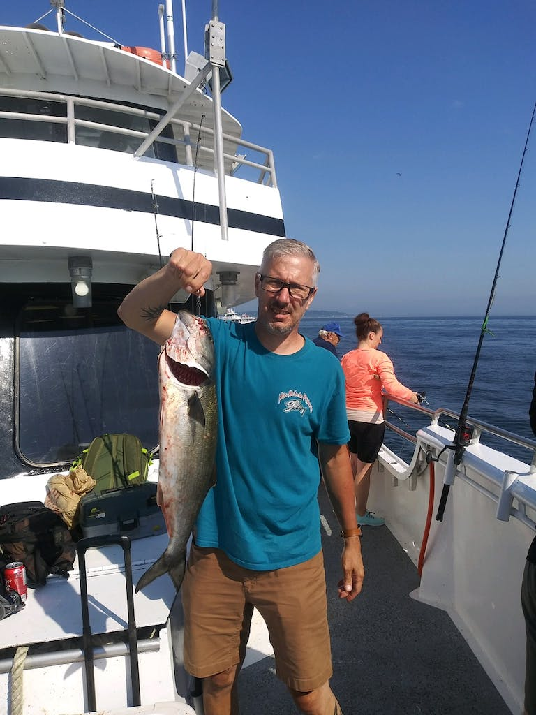a man holding a fish on a boat posing for the camera