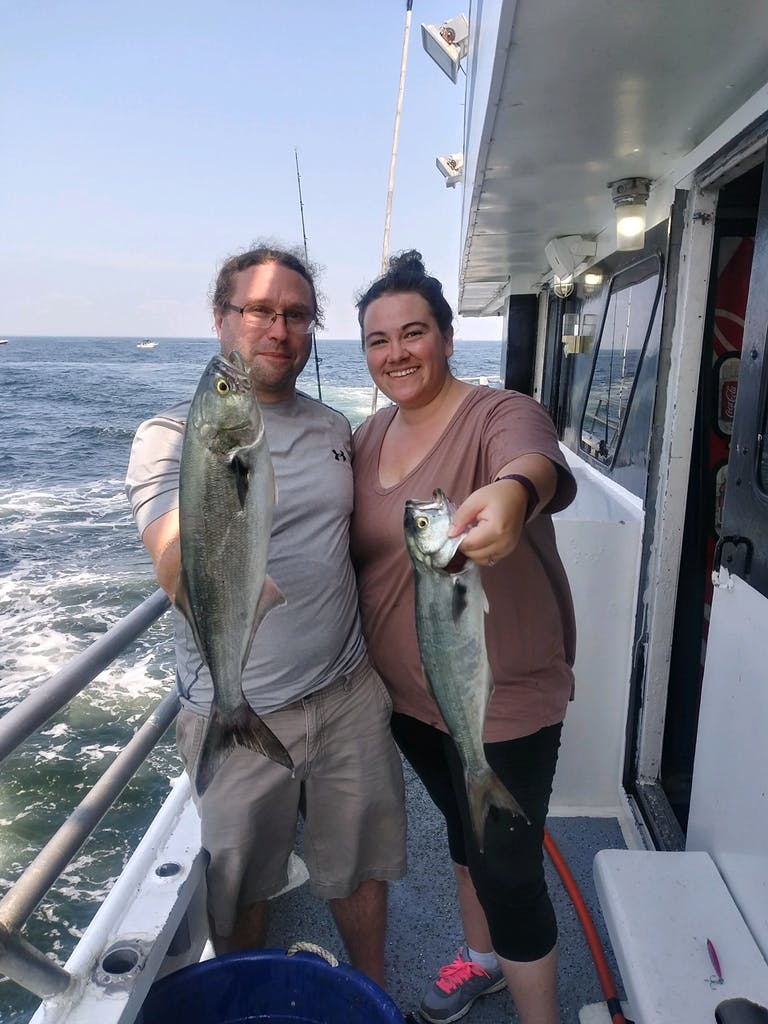Robyn Young holding a fish on a boat posing for the camera