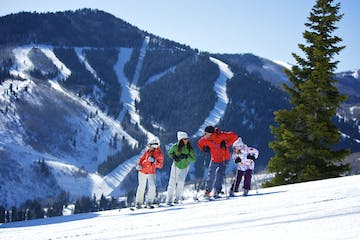 a group of people riding skis on top of a snow covered slope
